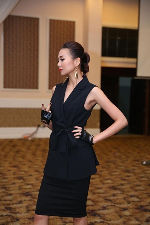 Cả cây đen cực chất phối giữa áo vest không tay dáng dài cách điệu và chân váy bút chì. Bộ trang phục kết hợp hài hòa giữa sự điệu đà, nữ tính pha chút mạnh mẽ, nam tính bởi những phụ kiện đi kèm.