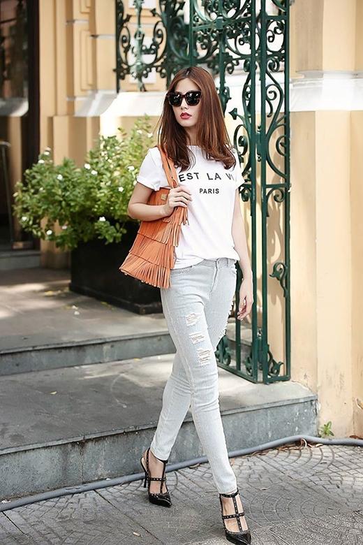 Diễm My 9X nhẹ nhàng, thanh lịch với áo phông trắng sơ vin lưng chừng cùng quần jeans bó sát. Trong khi đó, chiếc túi xách tua rua hợp mốt cùng giày sandal chiến binh lại thể hiện chút cá tính, mạnh mẽ trong phong cách của người phụ nữ hiện đại.