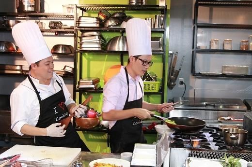 Hai người đàn ông hào hứng vừa nấu ăn vừa hát trong nhà bếp.