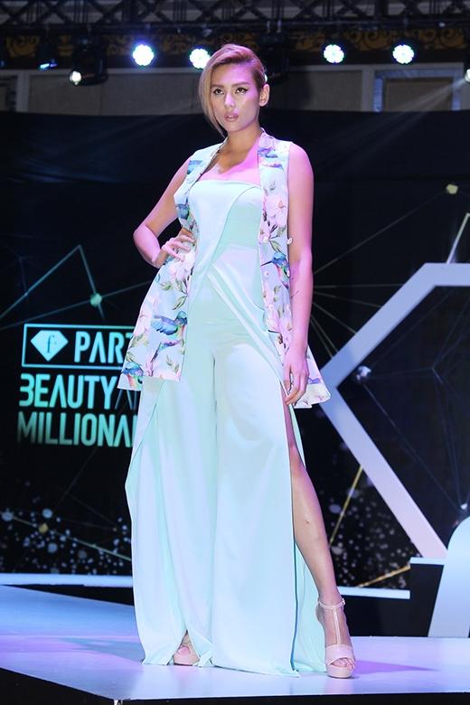 Chân dài Hoàng Yến mang đến sự kết hợp lạ mắt giữa jumpsuit xẻ tà và blazer không tay khoác ngoài.
