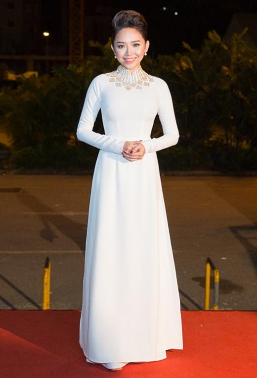 Tóc Tiên nền nã, duyên dáng trong tà áo dài trắng tinh khôi tạo điểm nhấn bởi chi tiết ánh kim vòng quanh cổ do Lý Quý Khánh thiết kế.