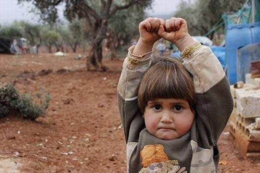 """Đây là """"em bé đầu hàng""""Adi Hudea. Bé mới 4 tuổi, là người Syria. Bé giơ tay và mím chặt môi vì tưởng máy ảnh là súng của những kẻ khủng bố. Hình ảnh được chụp tại trại tị nạn Atmen ở biên giới Syria - Thổ Nhĩ Kỳ."""