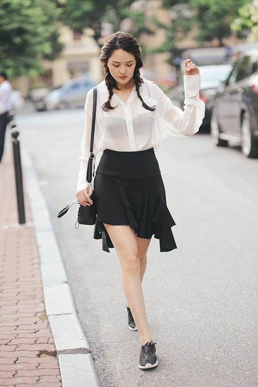 Táo bạo, trẻ trung sẽ là những hình dung rõ nét nhất về sự kết hợp giữa chiếc áo sơ mi trắng mỏng tang cùng chân váy bút chì được cách điệu lạ mắt của Hoàng Anh.