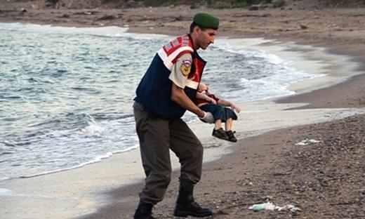 """""""Em bé Syria bên bờ biển"""" đang thu hút sự thương cảm từ rất nhiều người khắp nơi trên thế giới. Nó phản ánh một cách trung thực nhất thực trạng của cuộc khủng hoảng nhân đạo mà thế giới đang phải đối mặt trước dòng người di cư và tị nạn rất lớn đang đổ về Châu Âu. Em bé người Kurd, 3 tuổi có tênAylancùng mẹ và anh trai thiệt mạng trên đường chạy trốn khỏi cuộc chiến tại Syria."""