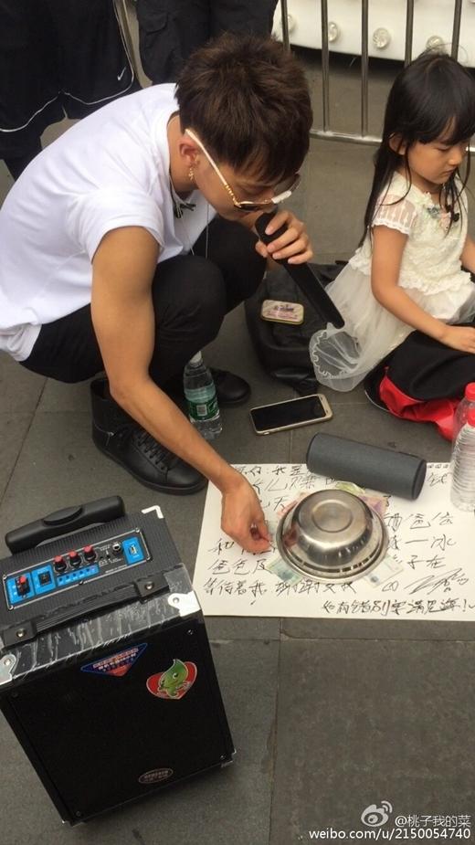 Tao viết trên giấy: ' Xin chào mọi người, tôi là ông bố trẻ Hoàng Tử Tao đây. Tôi đang rất đói vì phải tiết kiệm tiền để mua pizza cho con gái'.