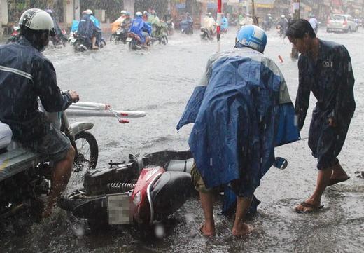 Một công nhân đang giúp người đi đường dựng xe lên. (Ảnh: Internet)