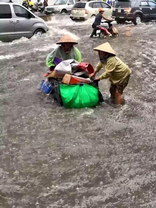 Hai người phụ nữ mua ve chai cố gắng vật lộn với dòng nước chảy xiết để giữ chiếc xe kiếm cơm hằng ngày khỏi trôi đi. Ảnh: FB