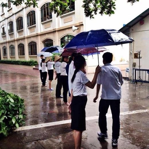 Các thầy cô đứng thành hàng rào làm mái che di động cho học trò nhỏ của mình. (Ảnh: FB)