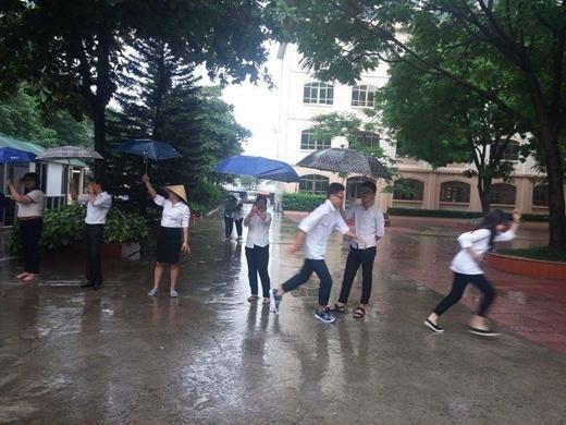 Không chỉ lo lắng học sinh của mình bị ướt, các thầy cô còn không ngừng nhắc nhở các em đi chậm kẻo ngã. (Ảnh: FB Lê Trung Quân).