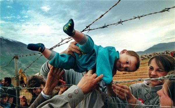 Một cậu bé 2 tuổi - con trai của người dân tị nạn trốn khỏi chiến tranh - được chuyền qua hàng rào gai an toàn trong cuộc chiến ở Kosovo.