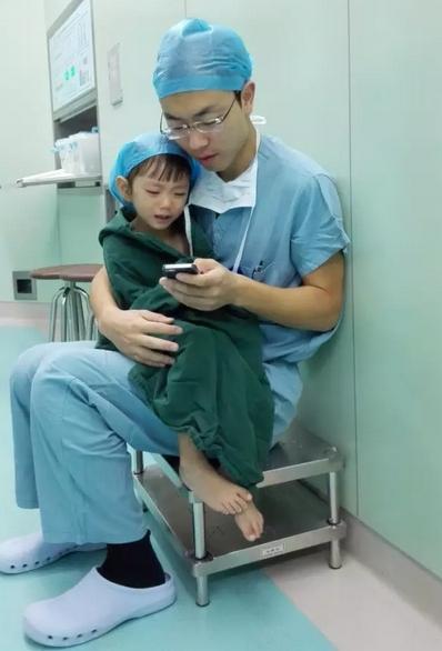 Hình ảnh vị bác sĩ trẻ ôm bé gái vào lòng vỗ về, trấn an em. (Ảnh: Internet)