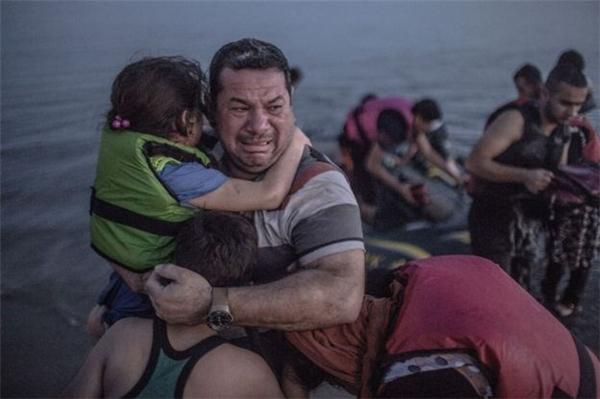 """Trong bức ảnh là người đàn ông Syria, Laith Majid, đang ôm lấy con trai và con gái mình sau khi kết thúc hành trình từ Thổ Nhĩ Kỳ tới đảo Kos của Hy Lạp trên một con thuyền chòng chành. Phóng viên ảnh người Đức Daniel Etter đã viết: """"Toàn bộ nỗi đau của một quốc gia hiện rõ trên khuôn mặt của một người cha. Tôi thực sự xúc động mạnh khi ghi lại cảnh tượng gia đình anh đoàn tụ trong nước mắt"""".(Ảnh Internet)"""