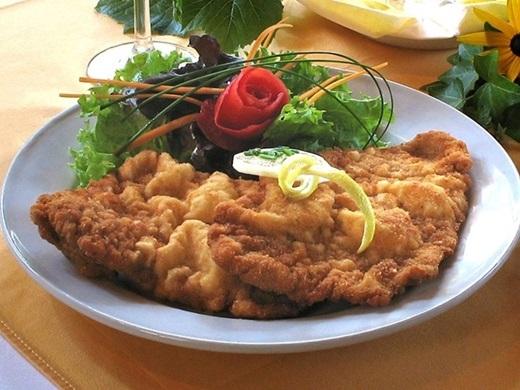 Wiener Schnitzel (Áo):Thịt bê được thái lát mỏng, tẩm vụn bánh mì và rán giòn, bày ra đĩa cùng chanh, rau mùi, khoai tây hoặc cơm.