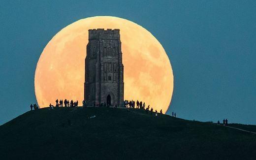 """Cảnh người dân háo hức với """"siêu Trăng máu"""" từ trên một đỉnh đồi ở Glastonbury Tor, Anh. (Ảnh: Telegraph)"""