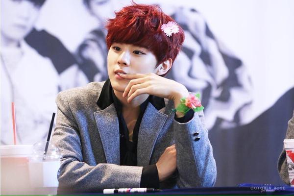 Mĩ nam Wooshin (UP10TION) không ngần ngại cài cả lông vũ và hoa hồng trên đầu trong khi tay lại đeo vòng lá nữ tính.