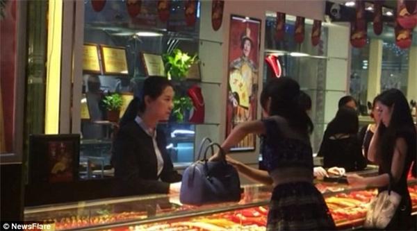 Người phụ nữ giàu có chuẩn bị lấy tiền từ túixách. Ảnh: Internet