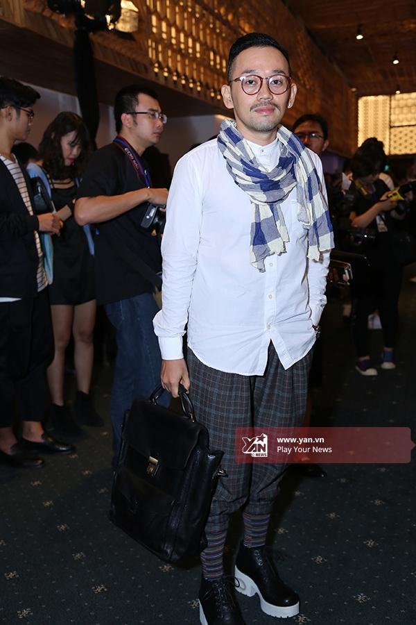Kan Kanemura - nhà thiết kế phụ kiện, nón từ ren nổi tiếng tại Việt Nam. Anh diện bộ trang phục thanh lịch, chỉn chu với điểm nhấn nhẹ nhàng ở chiếc khăn choàng kẻ sọc cùng giày da kết hợp tất nhiều màu.