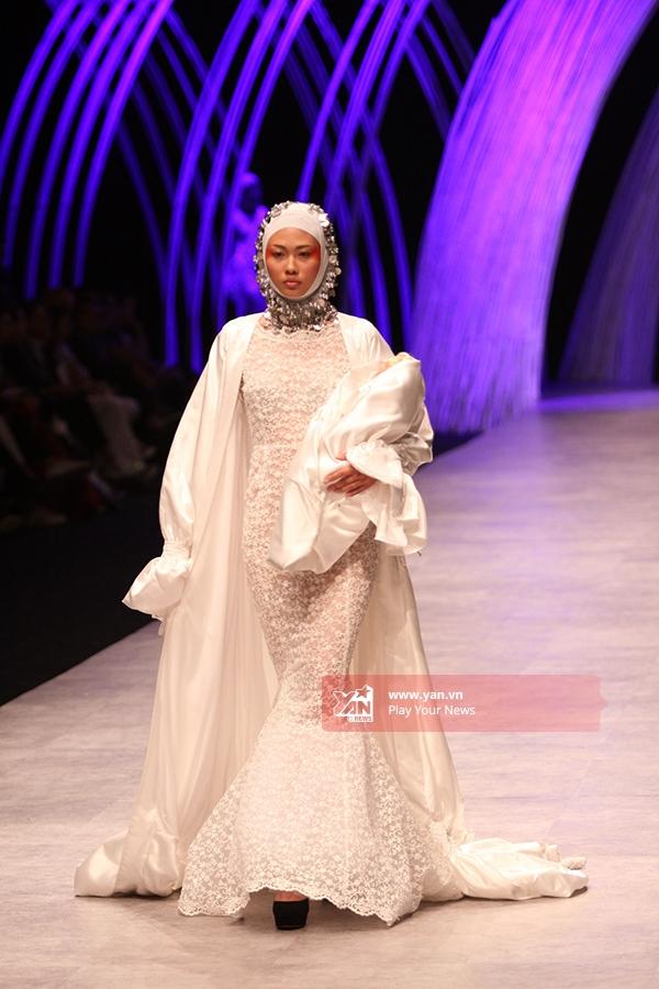 Mai Giang - Quán quân Vietnam's Next Top Model 2012- xuất hiện ấn tượng với vị trí mở màn trong bộ trang phục kết hợp giữa váy đuôi cá cùng áo choàng cổ điển, mang hơi thở của thời trang châu Âu những năm 60, 70.