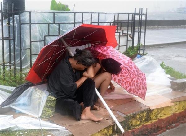 Cụ bà và người cháu co ro trong cái lạnh và gió giật mạnh tại Đại lộ Roxas. Ảnh: Internet