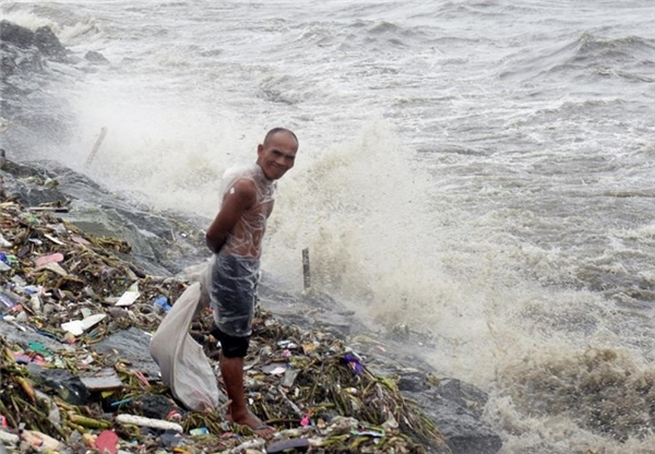 Người đàn ông này ra đứng quan sát thời tiết khi các cơn mưa lớn kèm gió mạnh đánh vào khu vực sông dọc đại lộ Roxas. Ảnh: Internet