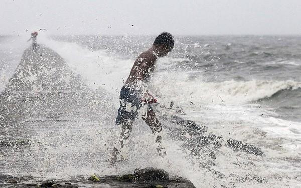 """Cậu bé """"liều mạng"""" đinhặt những chai nhựa ở bờ biển khi siêu bão Koppu đang vào đất liền. Ảnh: Internet"""
