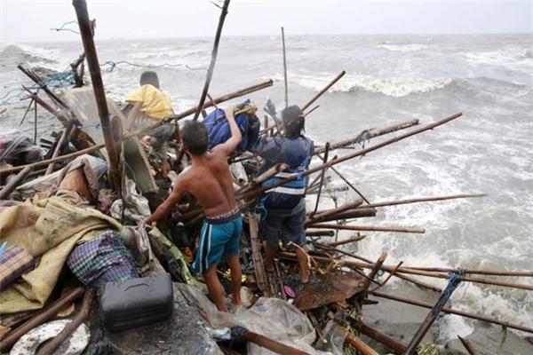 Nhiềuthành viên trong một gia đình gần Vịnh Malina đang cốvớt lạiđồ đạc sau khi nhà của họ bị nước cuốn trôi. Ảnh: Internet