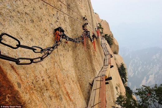 """Núi Hoa, Trung Quốc có mộtcây cầu nhỏ trên vách đá dựng đứng. Chắc chắn những ai có """"thần kinh thép"""" mới đi trên những miếng gỗ được ghép lại này. (Ảnh: Internet)"""