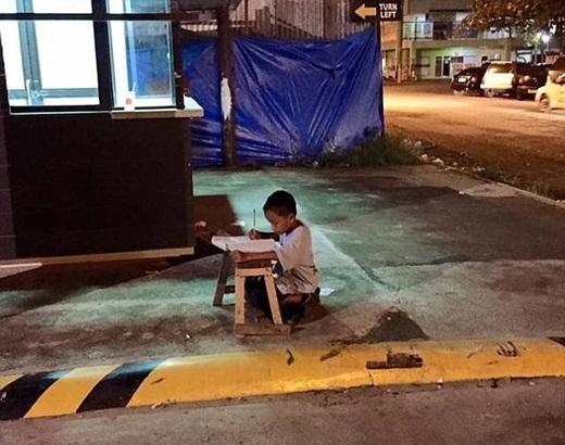 Bé trai mồ côi cha đang say sưa làm bài tập dưới ánh đèn đường. Ảnh: Internet