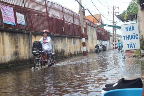Nước ngập sâu hơn nửa mét trên các tuyến đường, khiến sinh viên, học sinh đi học gặp nhiều khó khăn. Ảnh: GA