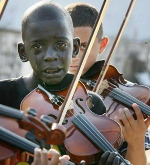 Cậu bé kéo đàn trong nước mắt tại đám tang người thầy dạy nhạc của mình.(Ảnh: Internet)