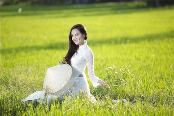Hoa hậu Diễm Hương diện áo dài trắng giữa hai biểu tượng quen thuộc của Việt Nam: nón lá và cánh đồng lúa.