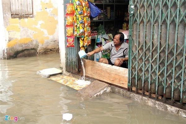 Người dân phải dùng vật chắn để ngăn nước tràn vào nhà. Ảnh: Zing/Tri thức trực tuyến