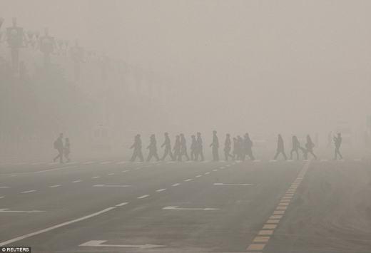 Người đi bộ cùng một cảnh sát băng qua Quảng trường Thiên An Môn, Bắc Kinh trong môi trường đầy bụi. Các trườnghọc đã phải hủy những chuyến dã ngoại cho học sinh cũng vì điều này.(Ảnh: Reuters)