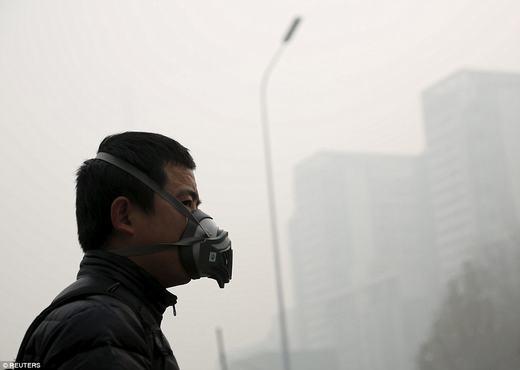 """Một người đàn ông phải đeo mặt nạ chống bụi khi ra đường. Ông chỉ là một trong số hàng triệu người Bắc Kinh đang phải sống chung với các """"phụ kiện"""" không lấy gì làm thích thú này.(Ảnh: Reuters)"""