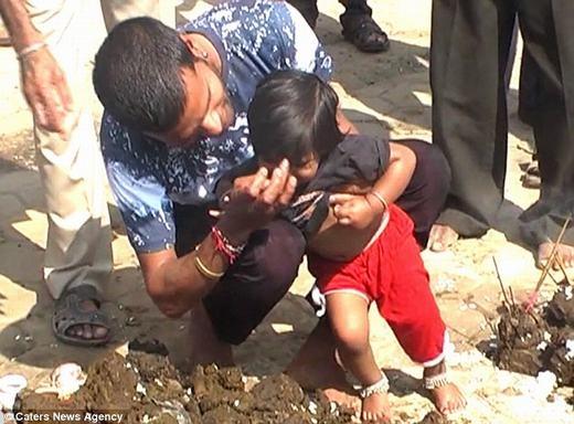 Một ông bố lấy phân bôi lên mặt con để được may mắn hơn. (Ảnh: CNA)
