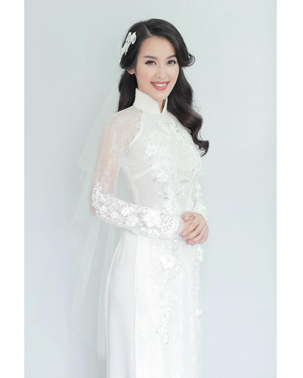 Toàn bộ trang phục cưới của Tú Vi đều lấy sắc trắng làm chủ đạo. Trong đó, bộ áo dài truyền thống được tạo điểm nhấn bởi những chi tiết ren đính kết tỉ mỉ, kì công trên nền vải voan mềm mại, sang trọng. Đặc biệt, Tú Vi dùng khăn voan trắng thay cho chiếc mấn đội truyền thống.