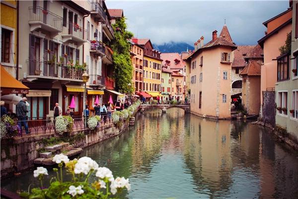 """Ở thị trấn cũ Annecy, Pháp, du khách sẽ được những ngôi nhà màu pastel chào đón cùng các quán cà phê đáng yêu trông ra bờ hồ. Ghé vào một quán ăn ngoài trời, đạp xe dọc theo bờ hồ hoặc thăm một số di tích lịch sử như Château d'Annecy… bạn sẽ không sợ """"rảnh rỗi"""" khi ở thành phố nhỏ này.(Ảnh: Internet)"""