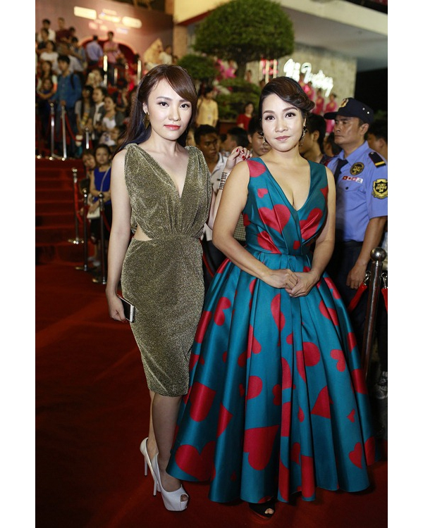 Tăng Thanh Hà và diva Mỹ Linh diện bộ váy xòe xẻ ngực sâu cùng những chi tiết gấp li tinh tế. Thiết kế tạo điểm nhấn bởi sự tương phản giữa nền xanh và họa tiết tim màu đỏ hồng.