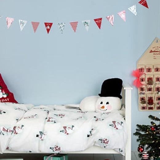 Treo những lá cờ tam giác lên đầu giường ngủ, thay ga giường, vỏ gối theo tông màu chủ đạo Giáng sinh.(Ảnh: BuzzFeed)