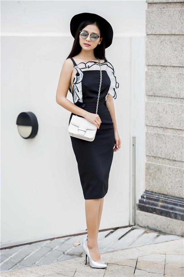 Chiếc váy đen ôm sát khoe đường cong nay đã trở nên lạ mắt hơn nhờ những chi tiết dún bèo độc đáo xung quanh.