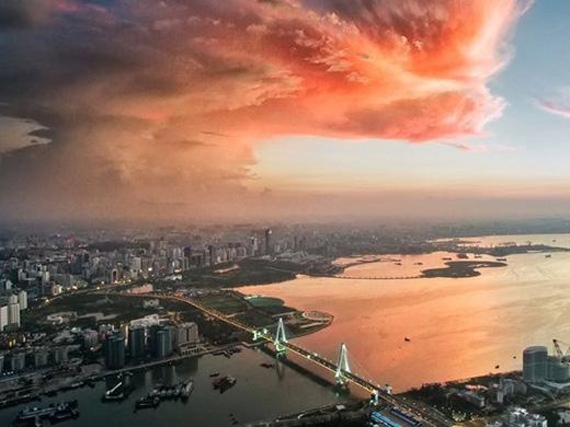 Đám mây sắc cam mang lại vẻ sinh động cho thành thị xám ngắt bên dưới.(Ảnh: Zifan Dong/SkyPixel)