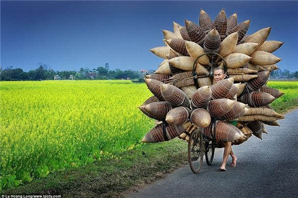 Bức ảnh được thực hiện tại làng Tất Viên, Hưng Yên. Chủ thể của bức ảnh – một ông lão chở những chiếc lờ bắtcá– gây ấn tượng mạnh mẽ với người xem. (Ảnh: Lý Hoàng Long)