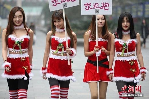 """4 cô gái giơ tấmbiển """"xin hãy ôm tôi""""đềuvô cùng xinh đẹp. (Nguồn Chinanews)"""