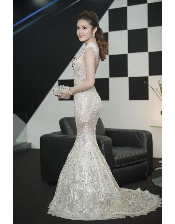 Thiết kế váy trắng với hàng loạt chi tiết đá quý đính kết bắt mắt của Á hậu Việt Nam 2014. Thay vào sự mềm mại thường thấy, bộ váy này lại được dựng phom cứng khá vững chắc.