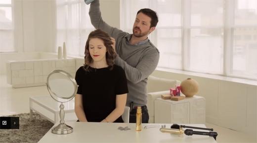 Tiếp tục xịt keo xịt tóc vào chỗ tóc vừa uốn xong. (Ảnh: Youtube)