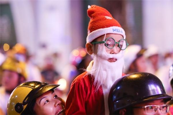 Em bé được người lớn cho mặc đồ ông già Noel đi chơi trên xe máy tại đường Đồng Khởi (quận 1). Ảnh:Hải An.