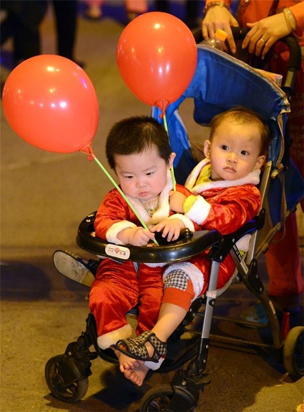 Thời tiết thủ đô ấm áp cũng làm cho lượng người đổ ra đường đông hơn bình thường. Các em nhỏ không phải mặc ấm, thoải mái ngồi xe đẩy dạo phố. Ảnh:Anh Tuấn.