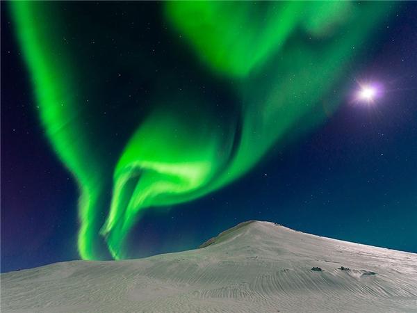 """Cực quang đang """"nhảy múa"""" cùng ánh trăng ở Iceland."""