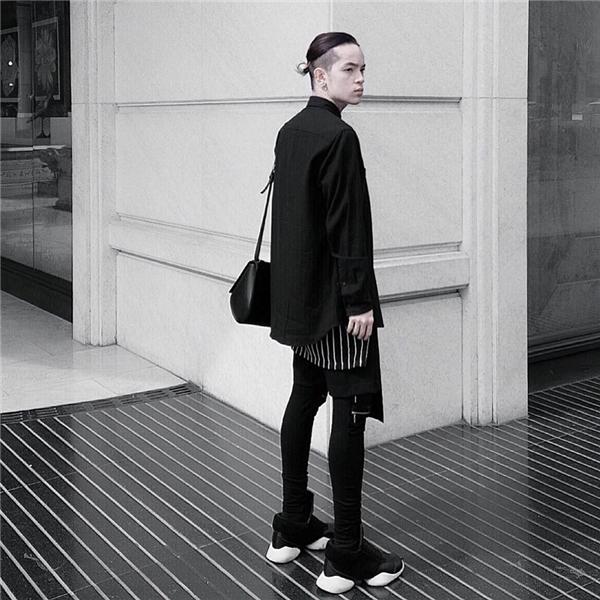 """Cả cây đen cầu kì của Kelbin Lei được tạo điểm nhấn bằng những chi tiết tông trắng xen kẽ. Để tạo nên tổng thể này, những """"nguyên liệu"""" mà Kelbin Lei sử dụng gồm có: quần skinny, áo phông dáng dài, áo sơ mi phom rộng cùng giày thể thao."""