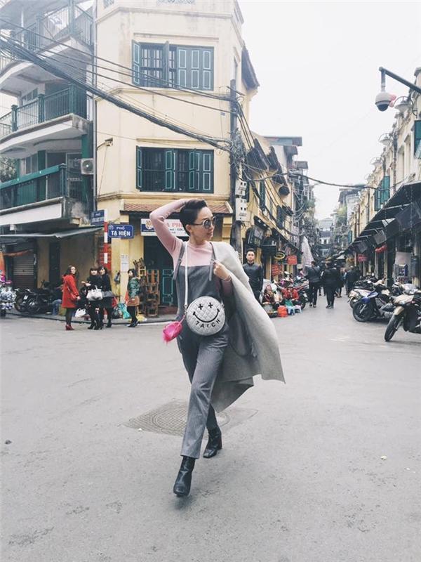 Trước đó, trên đường phố Hà Nội, Tóc Tiên lại vô cùng kín đáo, nhẹ nhàng với áo phông taydài cổ lọ kết hợp quần yếm và áo măng tô.